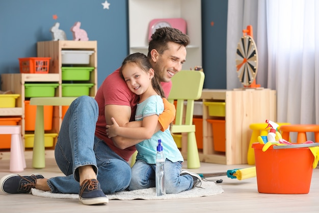 Happy father and daughter hugging after cleaning flat