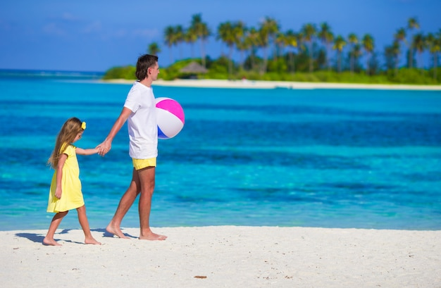Happy father and daughter playing with ball outdoor on beach