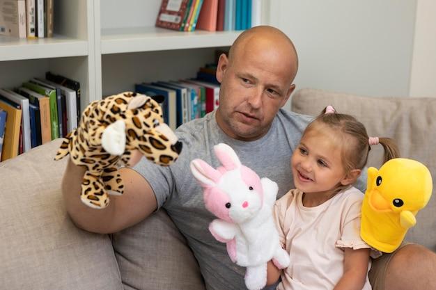 Padre e figlia felici che giocano con i burattini Foto Gratuite