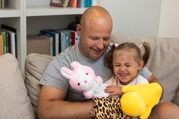 Padre e figlia felici che giocano con i burattini