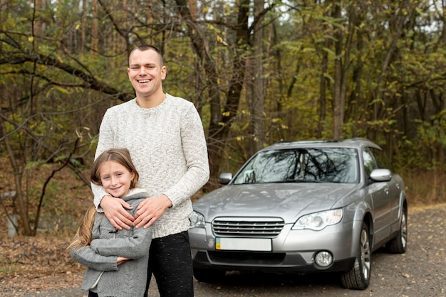Happy father and daughter standing in front of car
