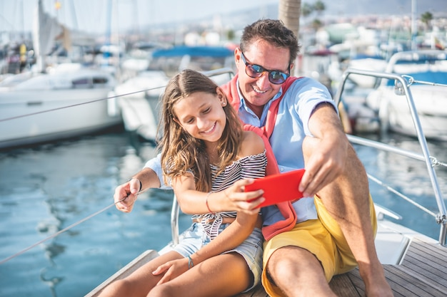 Happy father and daughter taking a selfie on sailboat during ocean trip vacation