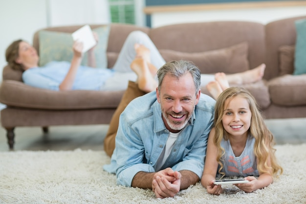 Happy father and daughter using mobile phone while lying on floor in living room