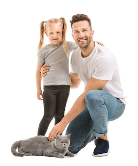 Happy father and daughter with cute cat on white