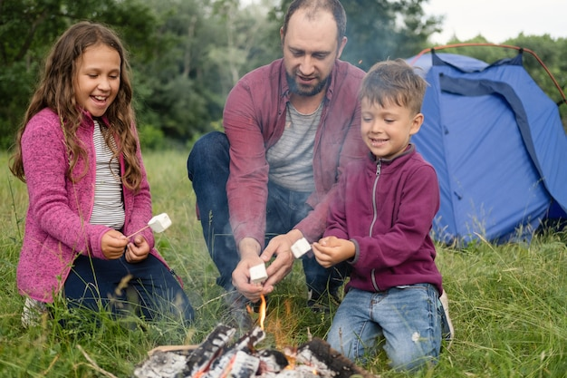 幸せな父、娘と息子は森のキャンプファイヤーでローストソーセージに座っています。テントの近く。父、親との余暇。幸せな家族の概念
