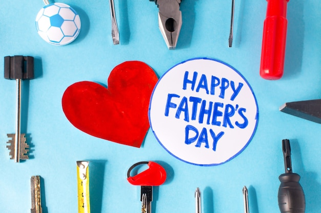 Happy father day flat lay. blue surface with tools and a heart with the inscription happy fathers day . copy space for text.