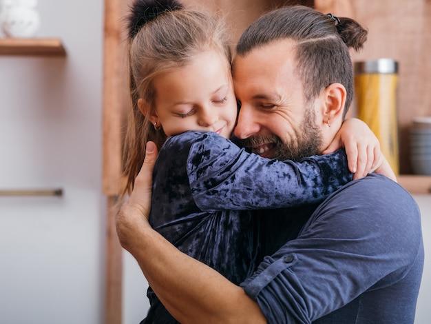 해피 아버지의 날. 사랑과 관심으로 그녀의 아빠를 포옹하는 귀여운 어린 소녀의 초상화.