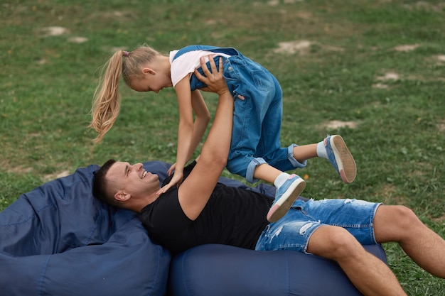 Happy father and doughter having fun and playing outdoors, sitting on frameless chair, spending time together in nature