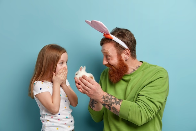 Happy father gives small fluffy rabbit to his daughter, makes present