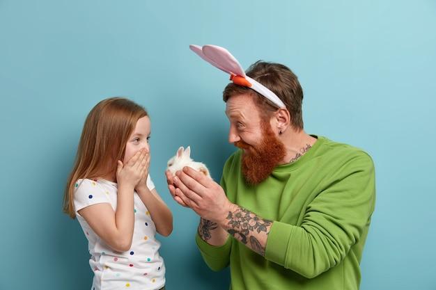 Счастливый отец дарит дочери маленького пушистого кролика, делает подарок