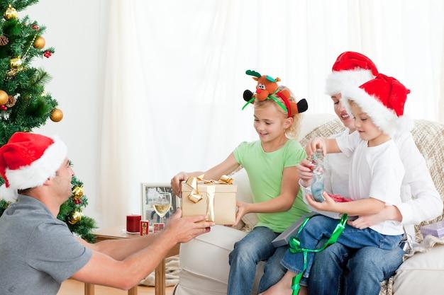 Счастливый отец дает подарок своей дочери, сидя на диване