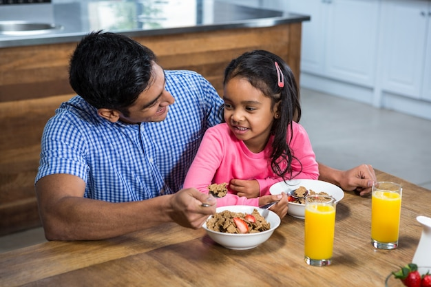 Happy father having breakfast with his daughter