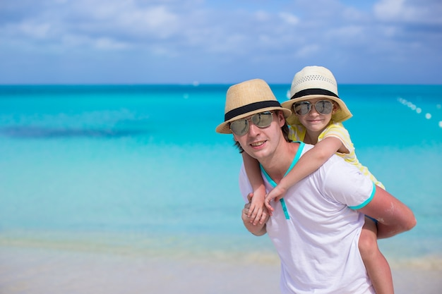 Happy father and his adorable little daughter have fun at tropical beach