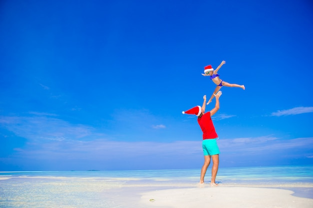 Happy father and his adorable little daughter in santa hat at tropical beach