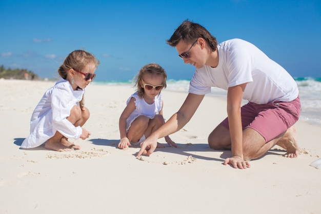 Happy father and his adorable little daughters playing on the beach