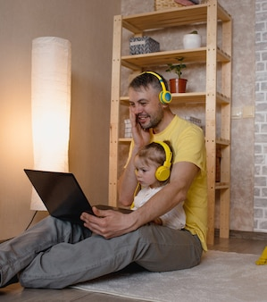 A happy father and his little daughter sit on the floor with yellow headphones and look in surprise at their laptop. the concept of family happiness
