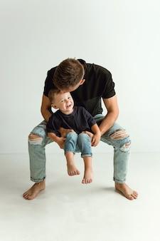 愛らしい幼い息子を抱いて笑っている幸せな父。子供が遊んで笑っている若い親。家族のライフスタイル。父の日、一体感、親子関係、子供の権利の概念。