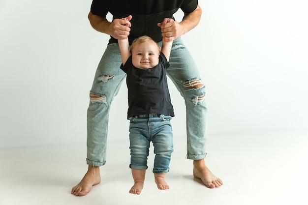 Padre felice che tiene in braccio un adorabile figlioletto e sorride