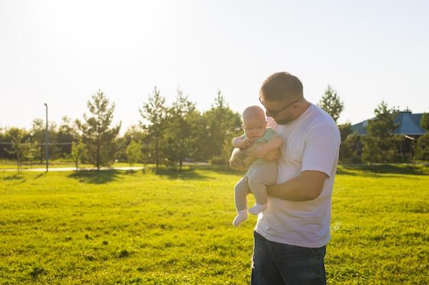 Счастливый отец держит маленького сына на природе концепция счастливого семейного дня отцов и ребенка