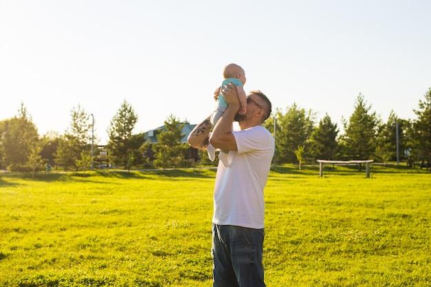 Счастливый отец держит маленького сына, бросая ребенка в воздух, концепция счастливого семейного дня отцов и ребенка