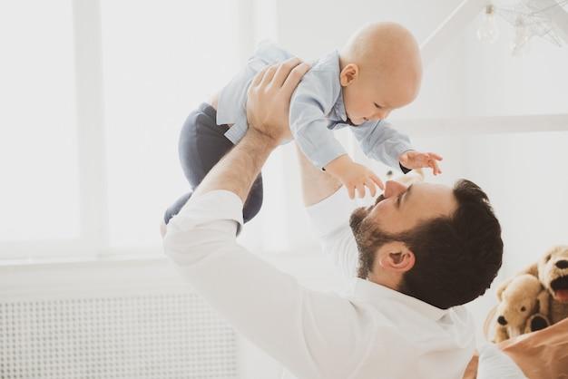 小さな赤ちゃんの息子を抱いて幸せな父。父権の概念