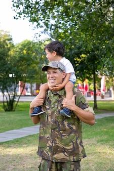 幸せな父は首に息子を保持し、彼の足を保持しています。公園で小さな男の子と一緒に歩いている制服を着た陽気な白人のお父さん。目をそらしているかわいい男の子。家族、父性、帰国の概念