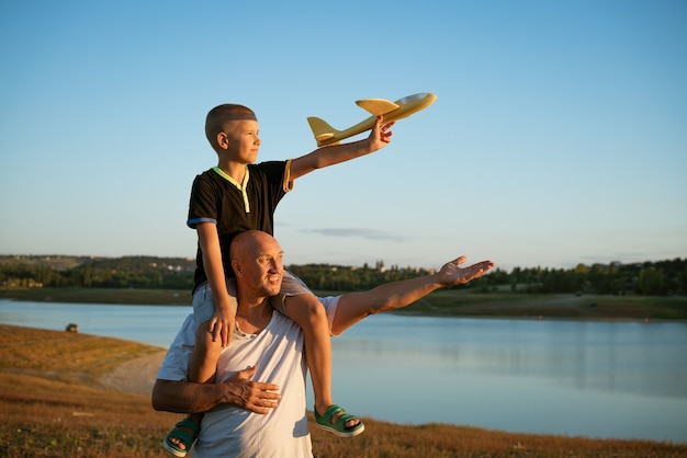 Happy father holding son on shoulders at sunset with airplane in hand concept of relationship with children