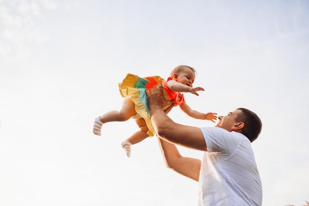 Il padre felice tiene la bambina affascinante su sotto il cielo dell'estate