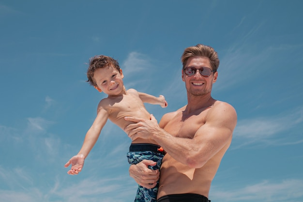 Happy father holds his little son in his arms on the beach with the ocean and beautiful blue sky on the background.