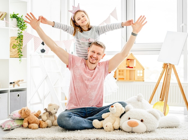プレイルームで美しい小さな娘を抱いて幸せな父