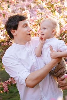 Счастливый отец в белой рубашке держит сына на руках, играя с ним на фоне палисандра в саду