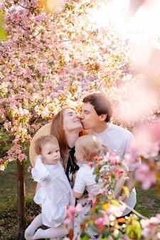 Счастливый отец целует любимую жену в щеку, держа на руках своих замечательных детей
