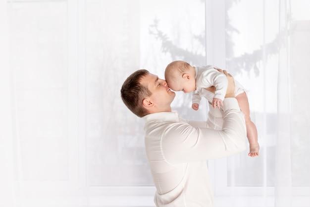 幸せな父は窓のそばで生まれたばかりの赤ちゃんにキス、幸せな愛情のある家族の概念、父の日