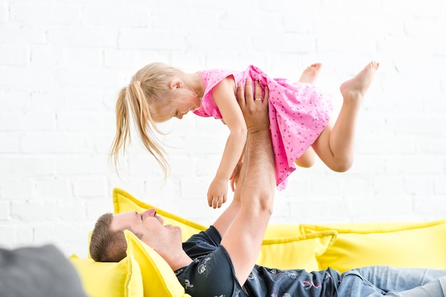 Happy father lifting her cute girl on sofa at home
