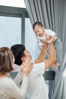 어머니가 그녀의 관심을 끌기 위해 손을 박수 할 때 그의 어린 딸을 들어 올리는 행복한 아버지