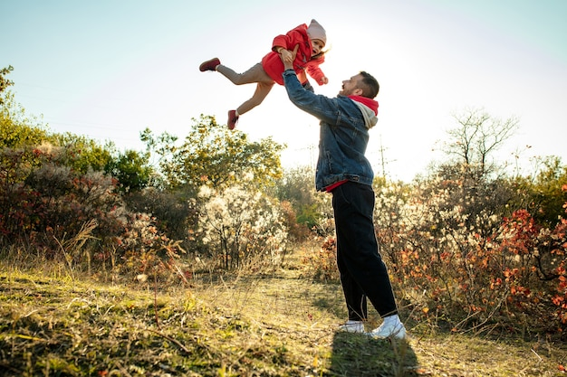 Happy father and little cute daughter walking down the forest path in autumn sunny day