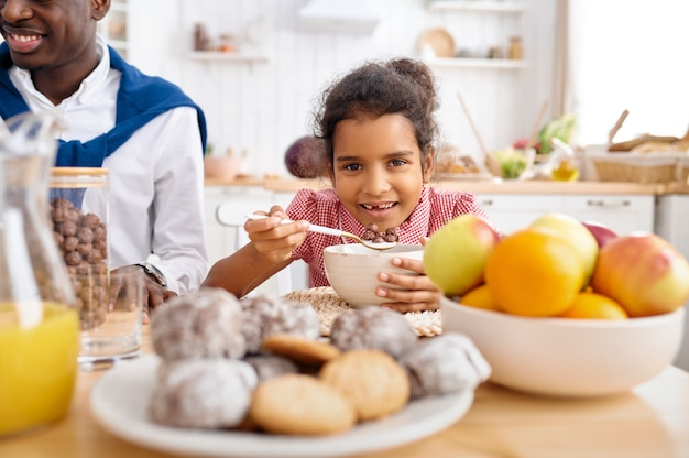 Happy father and little daughter eats flakes on breakfast. smiling family eats on the kitchen in the morning. dad feeds female child, good relationship