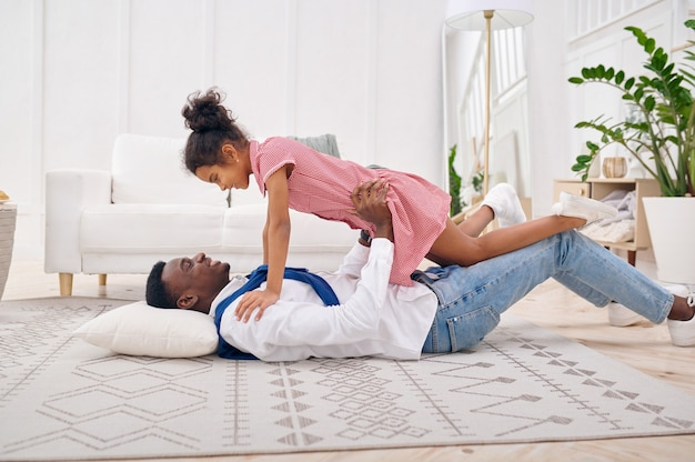 Happy father and little daughter play in living room