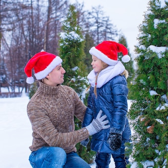 Happy father and little girl in santa hats with christmas tree outdoor