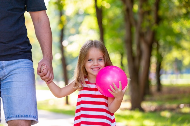 Happy father and little girl walking holding in hand in the summer park