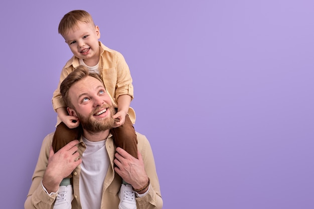 Happy father and little son posing at camera smiling, young caucasian family dad and son in casual wear isolated on purple wall