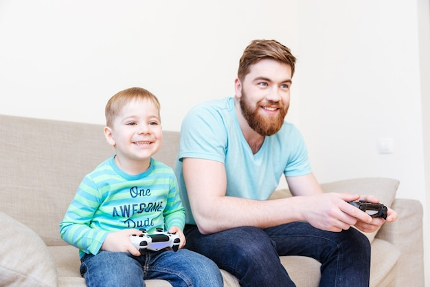 Happy father and little son sitting and playing video games on sofa at home