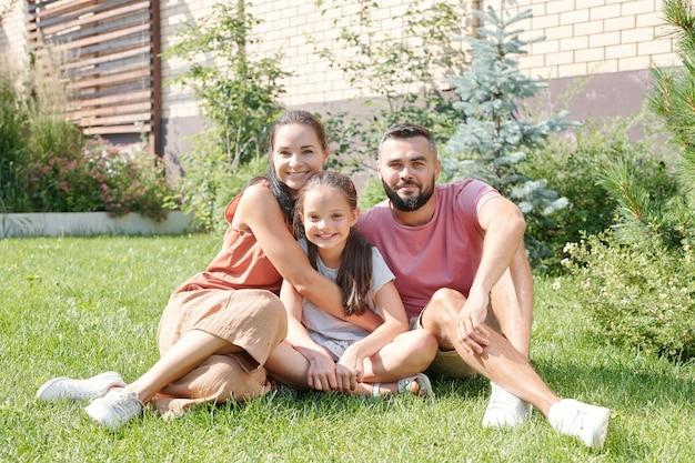 幸せな父、母と娘が笑顔で芝生の上に座って裏庭で一緒に時間を過ごす