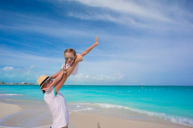 Happy father play with little daughter on their summer vacation