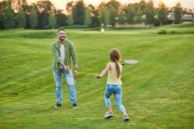 夏の日に公園で屋外で彼の楽しい小さな娘とバドミントンをしている幸せな父