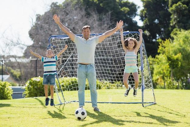 彼の息子と娘と一緒にサッカーをして幸せな父