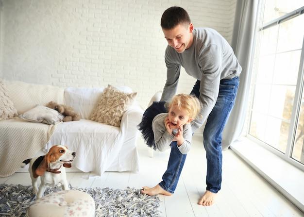 Счастливый отец играет со своей маленькой дочерью в яркой гостиной