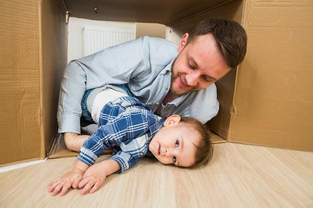 Padre felice che gioca con suo figlio bambino all'interno della scatola di cartone in movimento