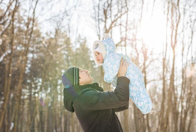 ウィンターパークで小さな子供息子の男の子と遊ぶ幸せな父。