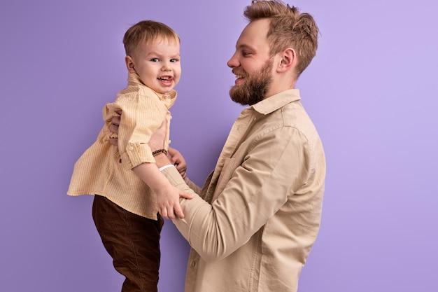 息子、子供、家族の概念で遊ぶ幸せな父。ハンサムな男性の手に男の子を持って、笑顔